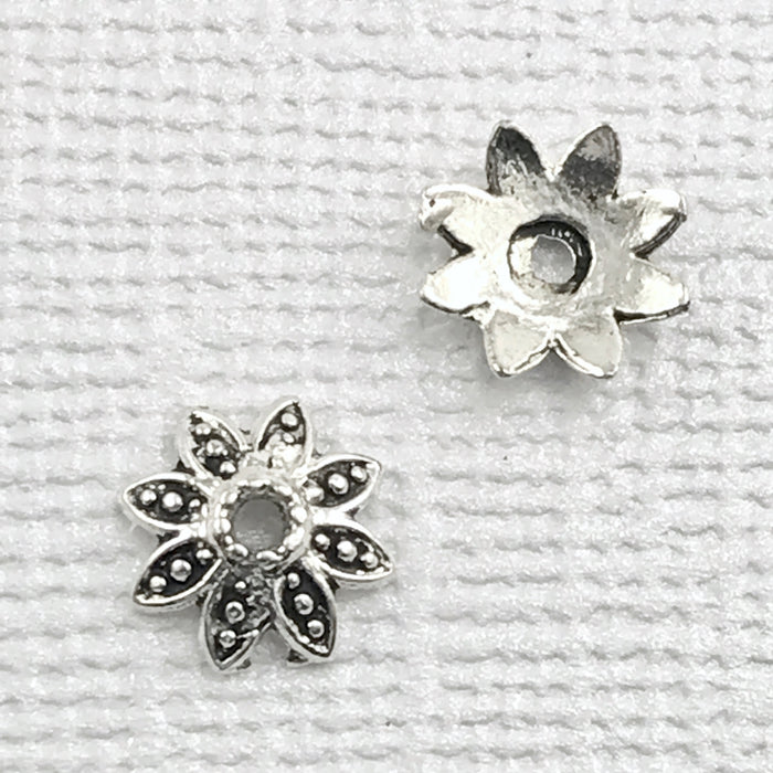 front and back of flower shaped silver bead caps