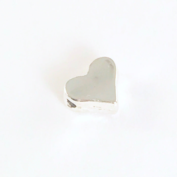 close up of a silver jewelry bead shaped like a heart