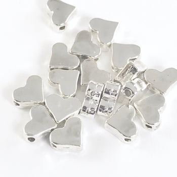 pile of silver jewerly beads shaped like hearts