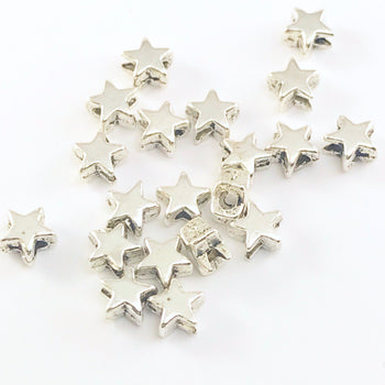 pile of silver jewerely beads shaped like stars