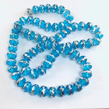 string of round jewelry beads that are light blue with silver stripe