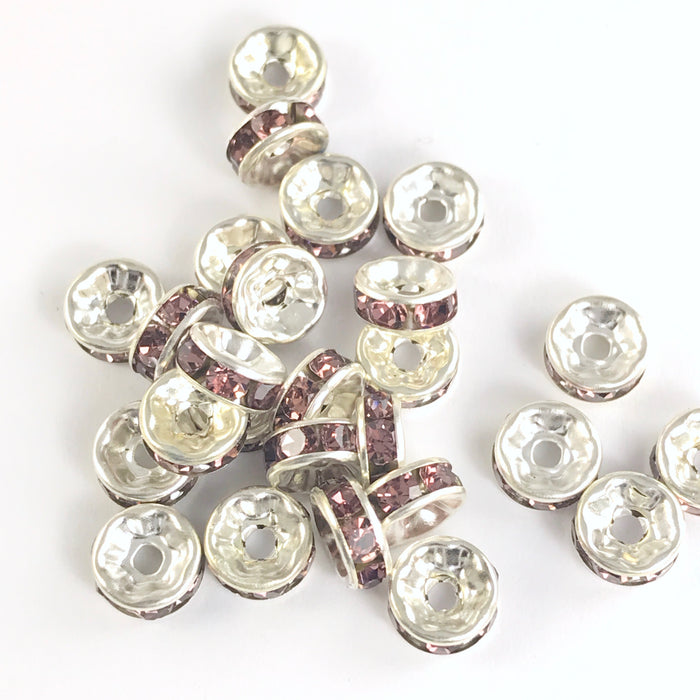 25 jewelry beads that are shiny silver with purple rhinestones