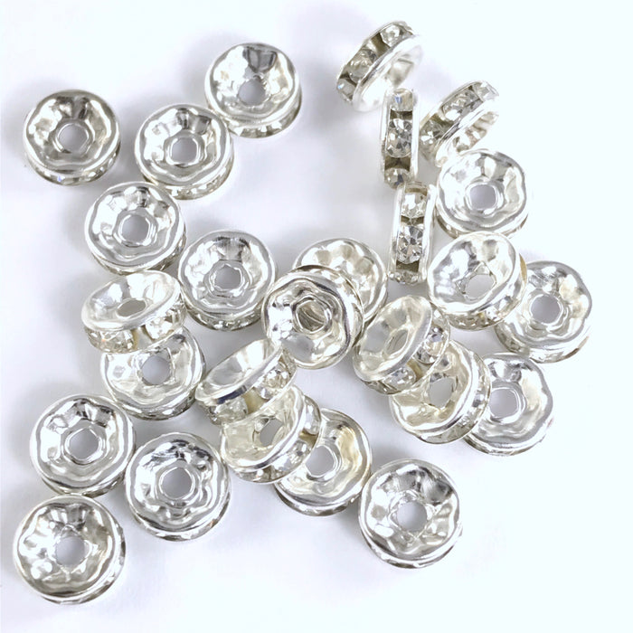 25 jewelry beads that are silver in colour with clear rhinestones