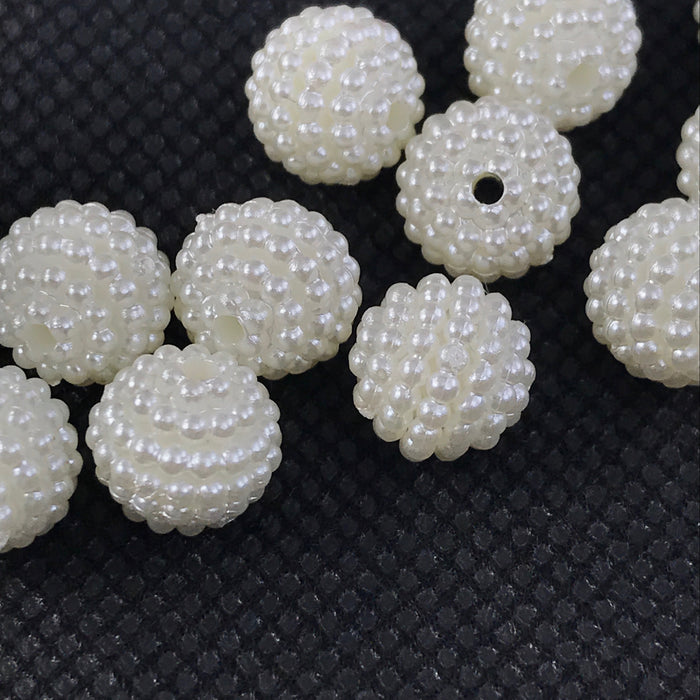 close up of round pearl colour beads on a black background