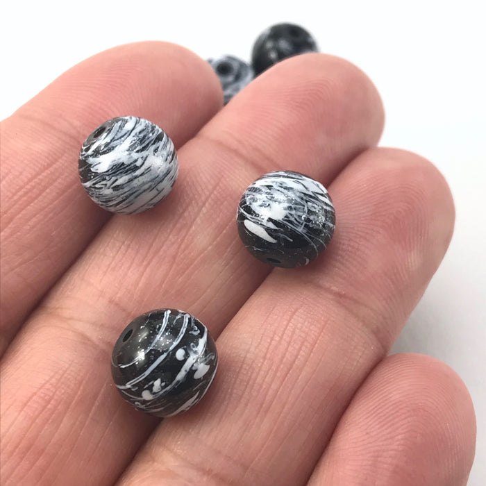 round beads with a black and grey marble design, sitting on hand