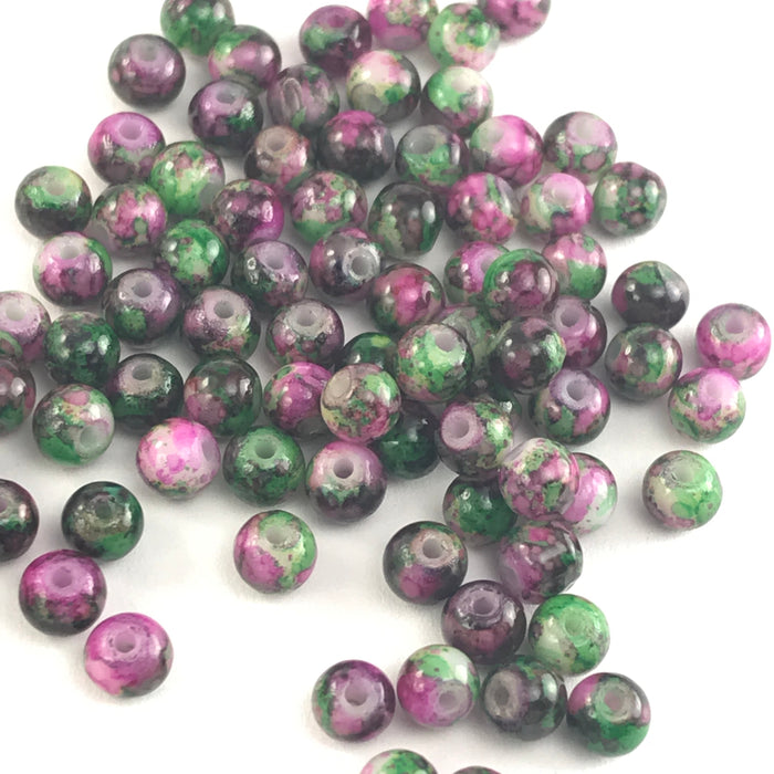 round jewelry beads that have a green and pink marbled appearance