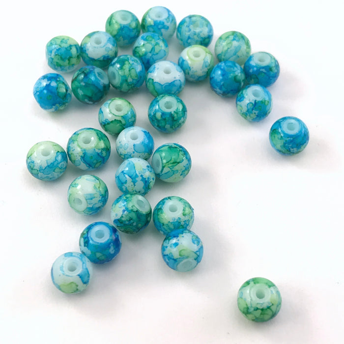jewelry beads that have a green and blue marble pattern