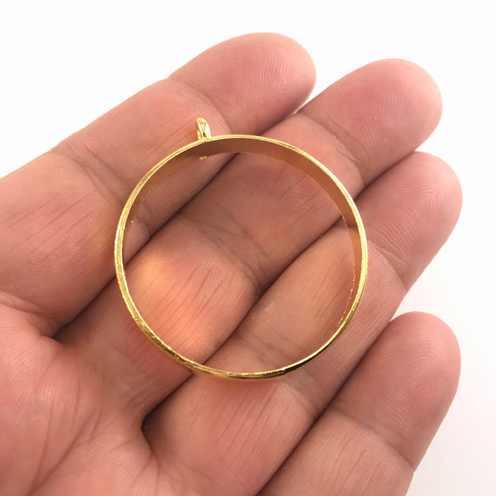 round gold open back bezel sitting on a hand