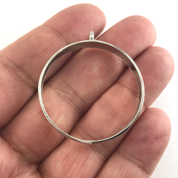 silver colour open bezel with a loop, sitting on a hand to show scale