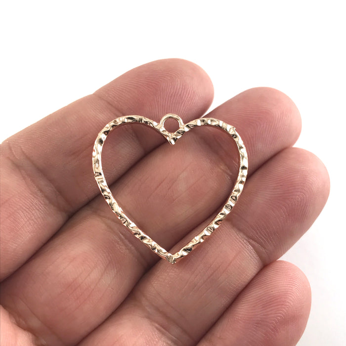 heart shaped rose gold open bezel sitting on a hand to show scale