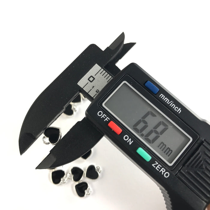 black and silver heart shaped jewerly charms, on a digital ruler that reads 6.8mm