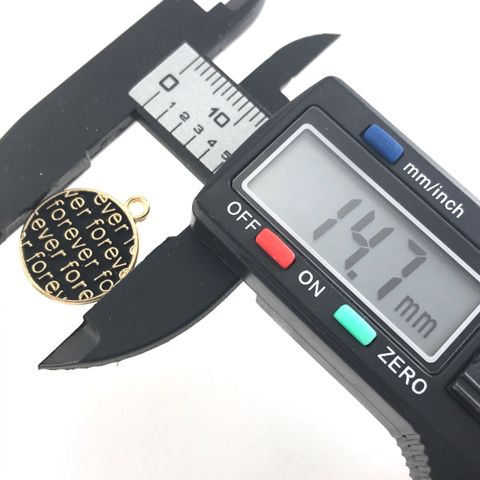 round black and gold charms with the word forever on them on a digital ruler that reads 14.7mm