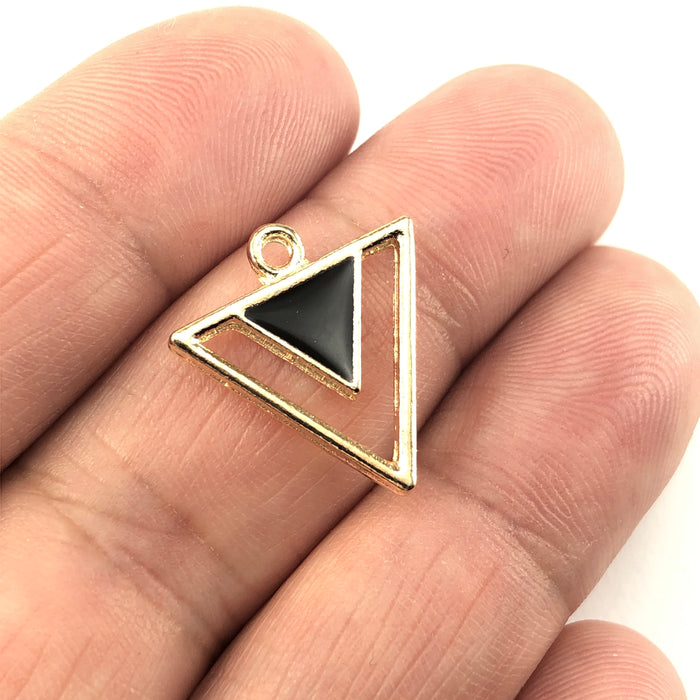 black and gold triangle shaped jewerly charms, sitting on a hand to show scale