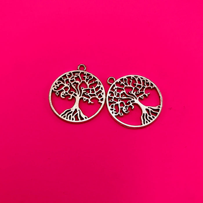 silver tree shaped jewelry charm on a pink background