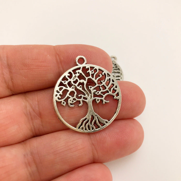 tree shaped silver jewelry charm on a hand