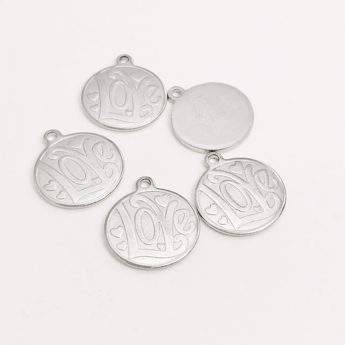 silver colour jewelry charms that have Love stamped on them