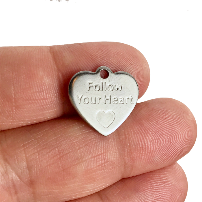 silver jewelry charm with follow your heart stamped on it on a hand