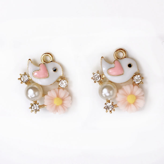 pink white and gold pendants of a bird with flower