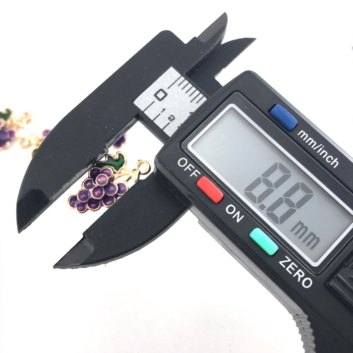 purple green and gold jewerly charms that look like a bunch of grapes, horizontal on a digital ruler that reads 8.8mm