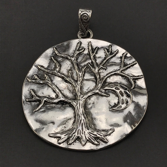 large silver jewelry pendant with tree of life on it