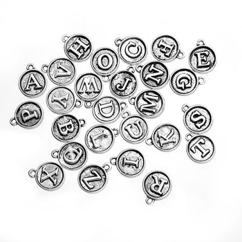 round silver jewelry charms with letters on them