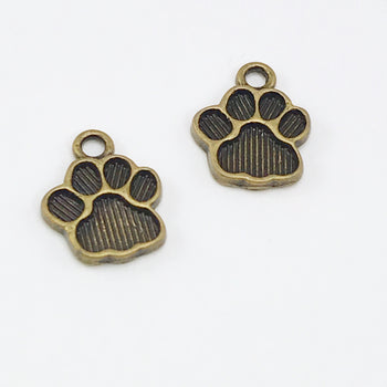 two jewelry charms that look like paw prints