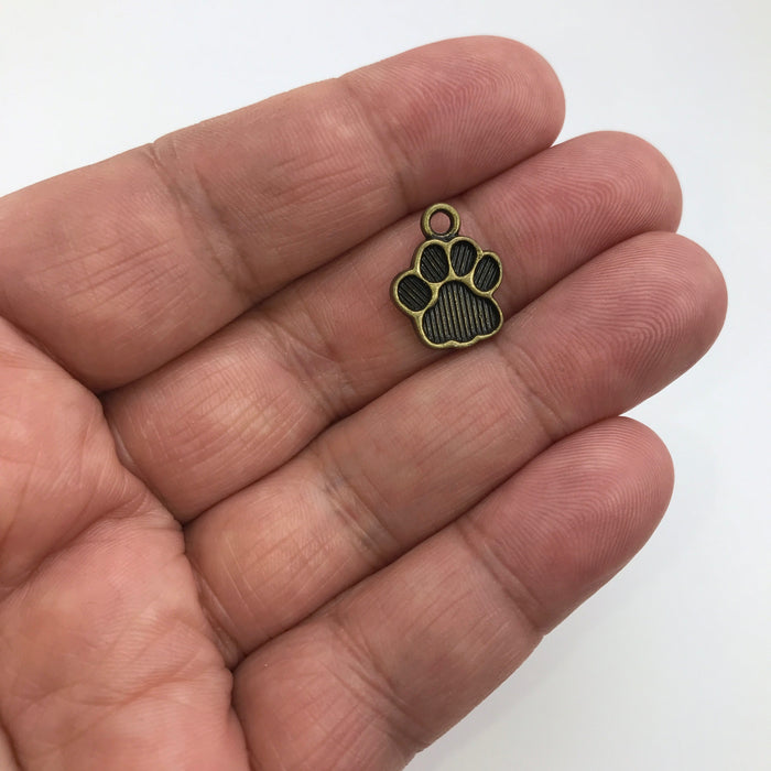 bronze jewelry charm that looks like paw print in hand