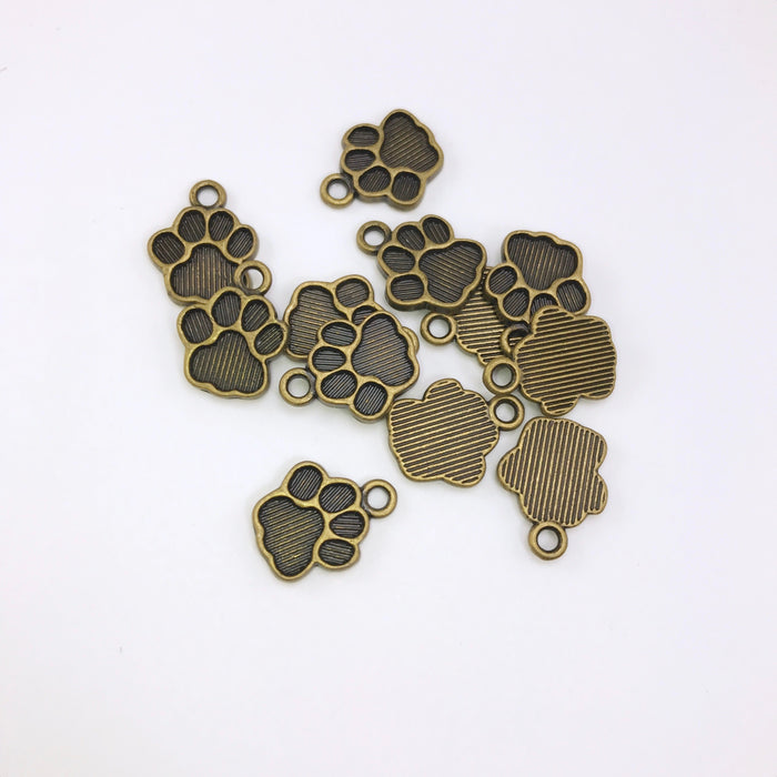 pile of bronze jewelry charms that look like dog paw prints