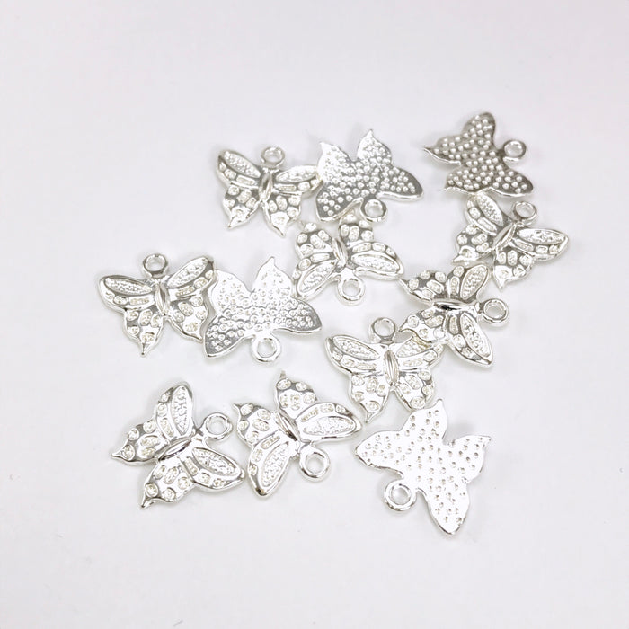 pile of silver jewelry charms shaped like butterflies