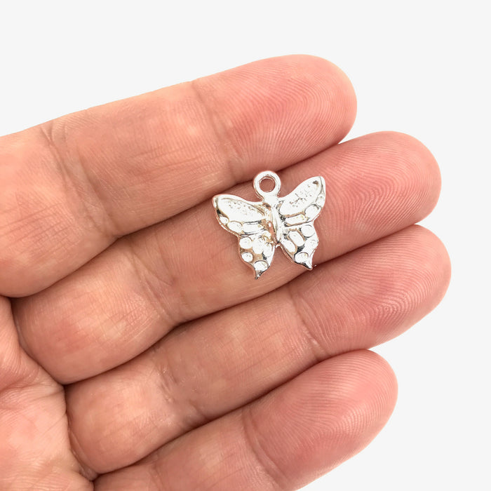 silver butterfly shaped charm on a hand