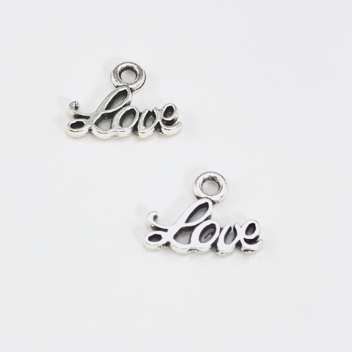 2 tiny jewelry charms that say the word love