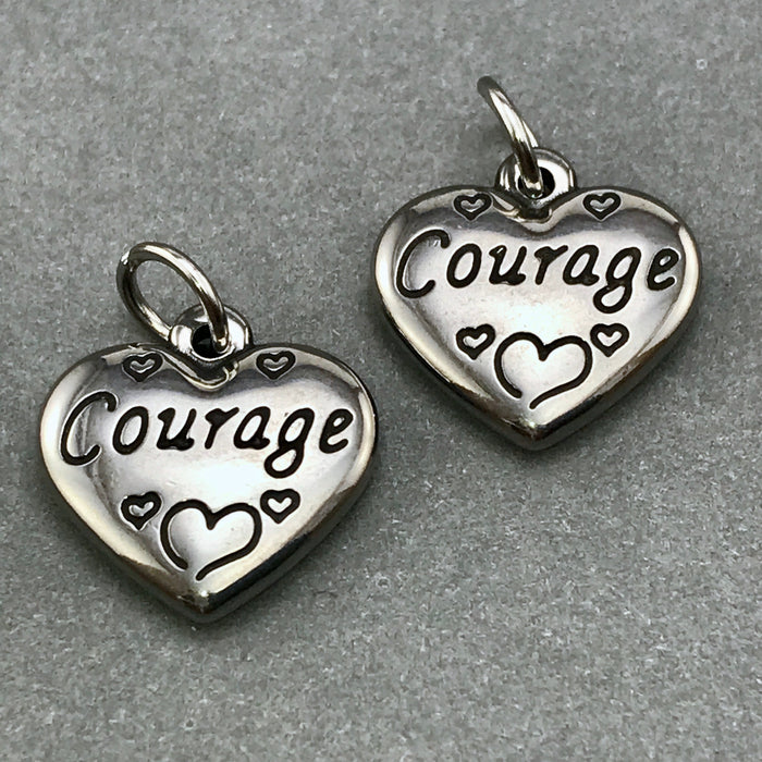 Two heart shaped jewelry charms with courage engraved on them