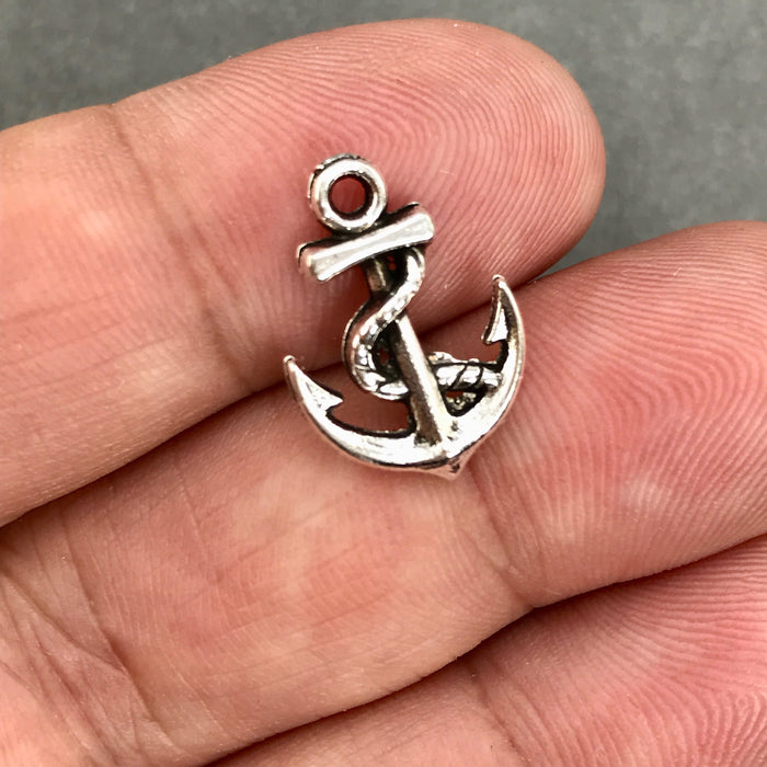 close up of antique silver anchor shaped jewelry charm on a hand
