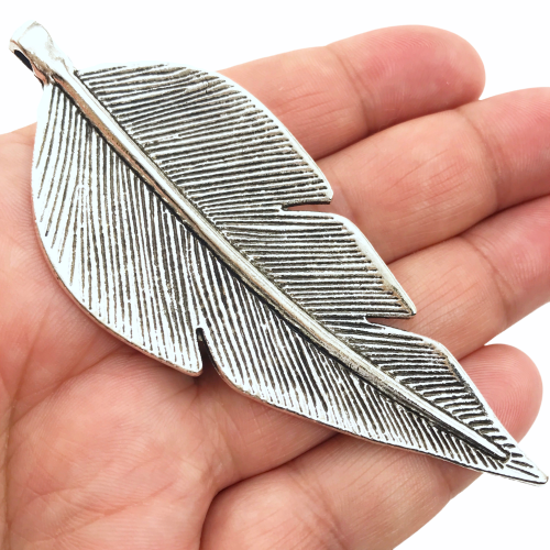 large silver jewelry pendant shaped like a leaf sitting on a hand