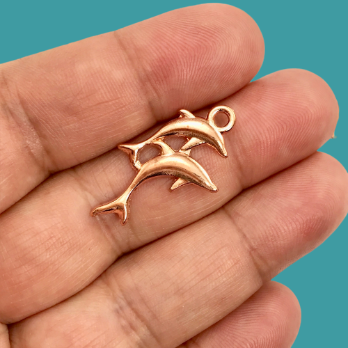 close up of rose gold dolphin shape jewelry charm on a hand