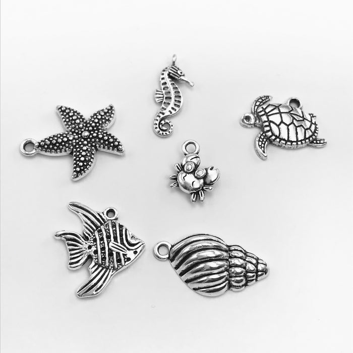 6 silver jewelry charms shaped like fish, seahorse, tortoise, seashell, crab, starfish