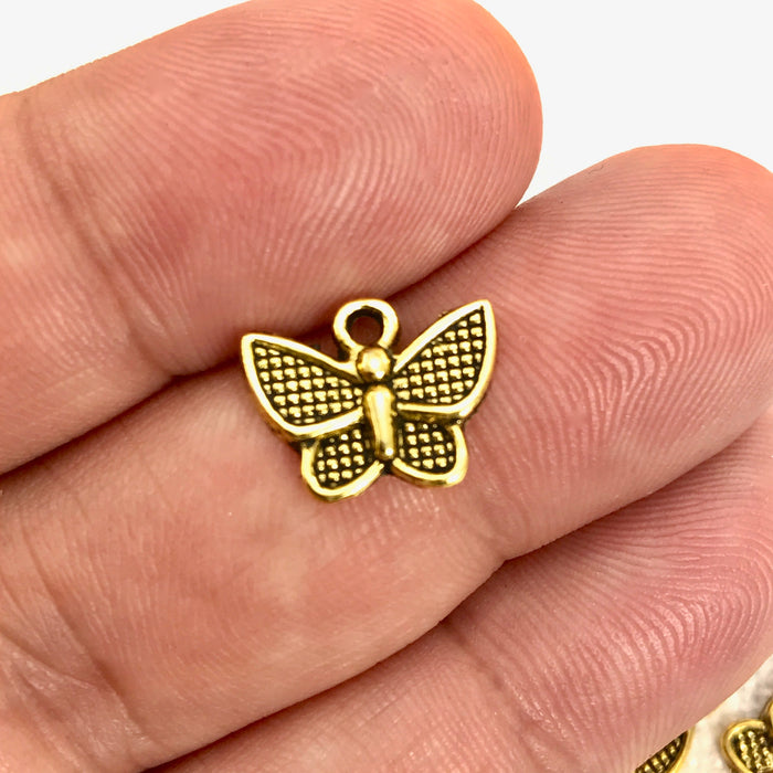 gold color butterfly shaped jewelry charm on a hand