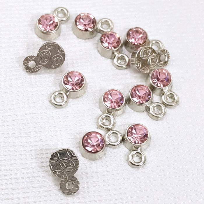 pile of silver jewerly charms with pink rhinestones