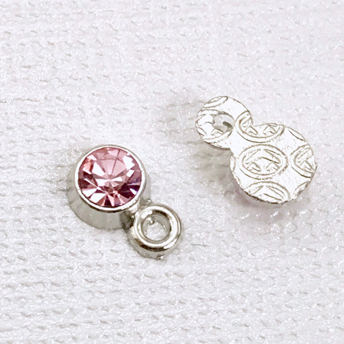 front and back of round silver charms with pink rhinestones