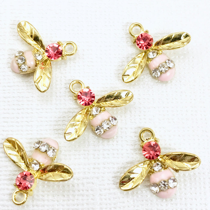 5 gold and pink jewelry charms that look like bees