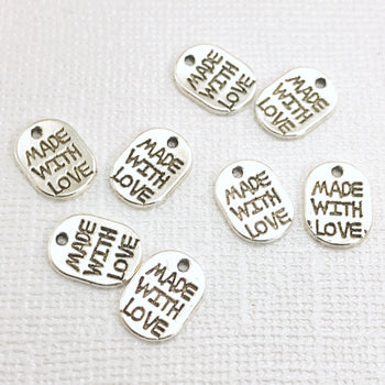 oval silver jewelry charms that have made with love stamped on them