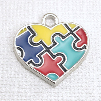 jewelry charm that is silver with multi color puzzle piece pattern