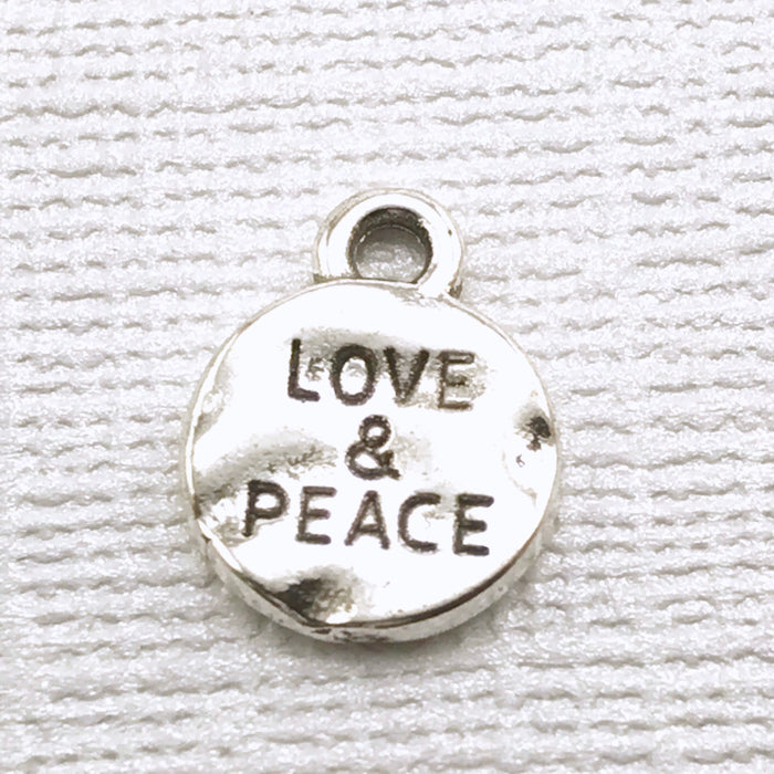 round silver jewelry charm with love and peace engraved in it