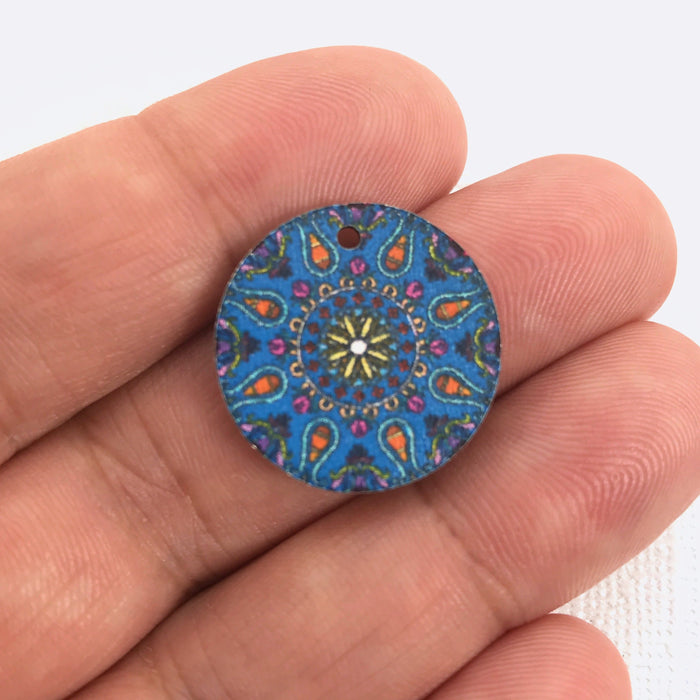 round wood jewelry charm with blue pattern printed on it. Sitting on a hand