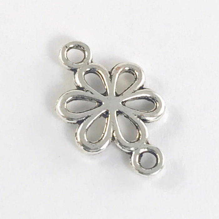 close up of a silver colour jewelry charm shaped like a daisy