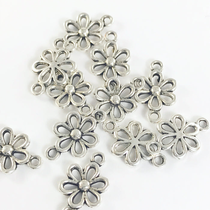pile of silver jewelry charms shaped like flowers