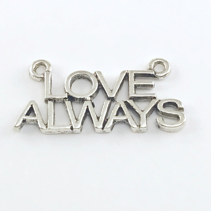 close up of a silver jewelry pendant that says love always