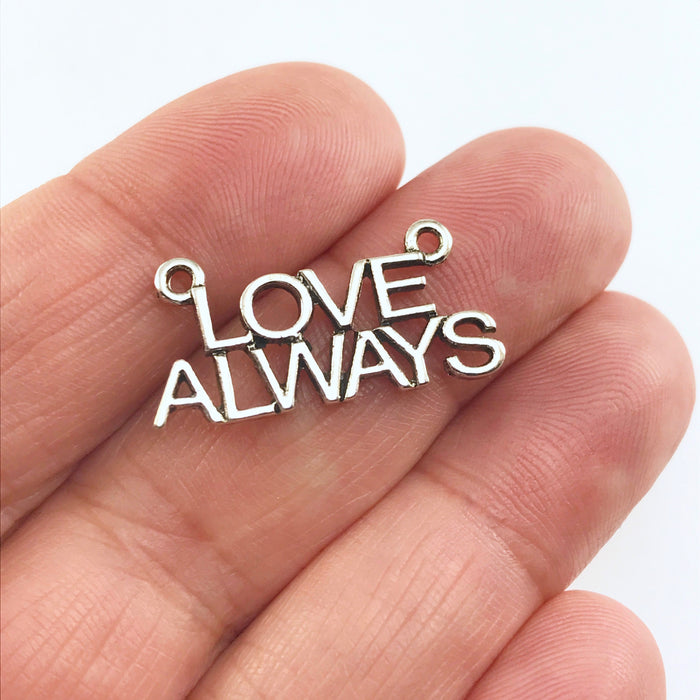 silver colour jewelry pendant charm that says love always sitting on a hand