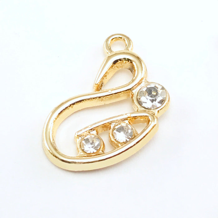 gold colour jewelry pendant that is shaped like a swan