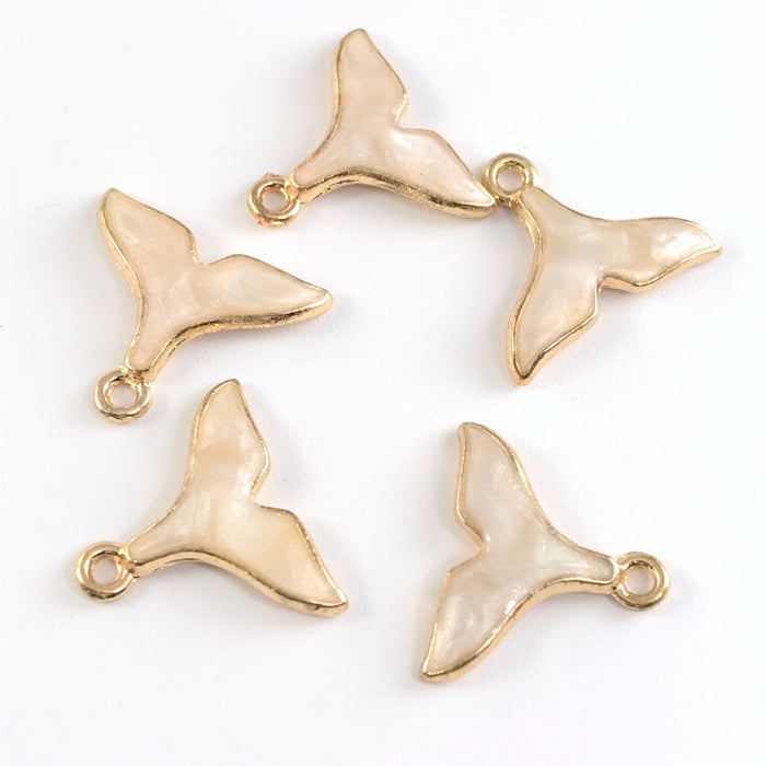 5 whale tail shaped jewelry charms in a beige colour